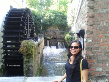 Posing with a watermill in the background
